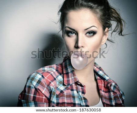 Beautiful teen girl inflating bubble of chewing gum. Modern fashion girl. Toned. - stock photo