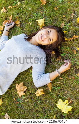 Beautiful teen girl on a green lawn with yellow leaves lying on his back - stock photo