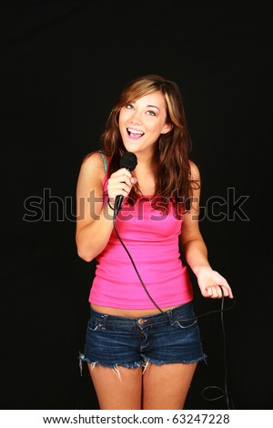 beautiful teen girl singing with microphone on black background