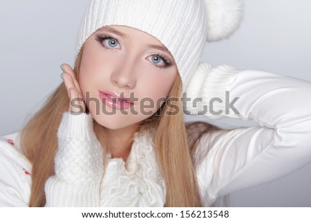 Beautiful teen girl wearing winter clothing and funny white hat. Isolated on grey background - stock photo