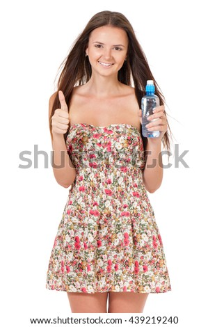 Beautiful teen girl with bottle of water showing thumb up, isolated on white background.
