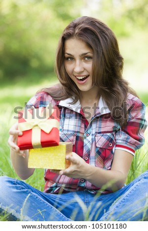 Beautiful teen girl with gift in the park at green grass. - stock photo