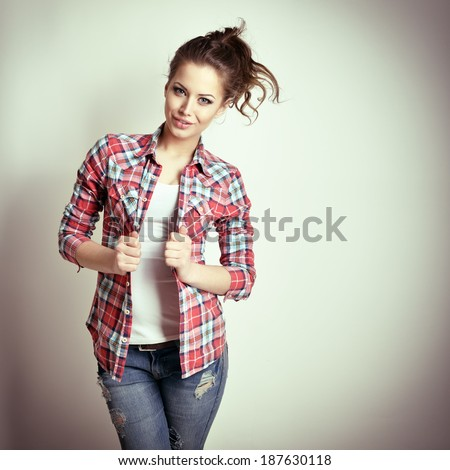 Beautiful teen girl with jeans and checkd shirt. Fashion girl. Toned. - stock photo