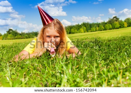 Beautiful teen girl with noisemaker horn and birthday party cap laying outside with happy expression on sunny summer day - stock photo