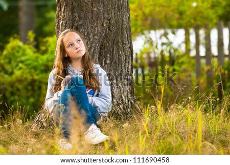Beautiful teen-girl writing in a notebook while sitting in the park (dreamily looks up)