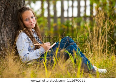 Beautiful teen-girl writing in a notebook while sitting in the park (looks into the camera) - stock photo