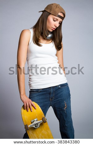 Beautiful teen skater girl holding skateboard - stock photo