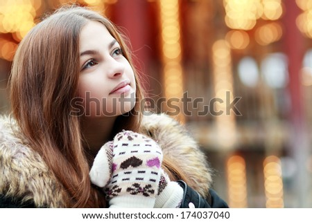 beautiful teenage girl against a background of city lights in the winter season - stock photo