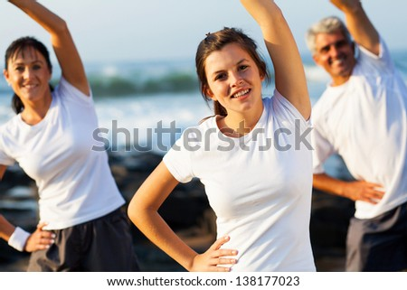 beautiful teenage girl and her parents working out at the beach
