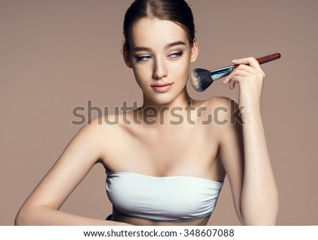 Beautiful teenage girl applying cosmetic powder on her face with tassel, skin care concept / photoset of attractive brunette girl on beige background - stock photo