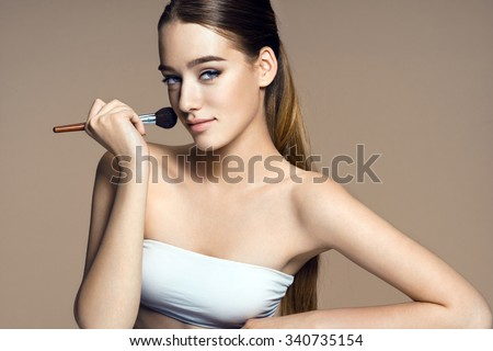 Beautiful teenage girl applying foundation on her face with tassel / photo-composition of brunette girl on beige background. High resolution product. - stock photo