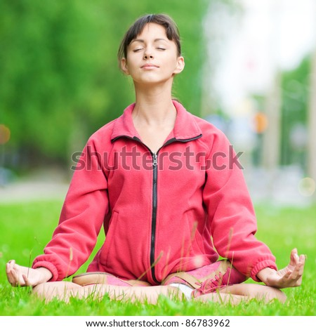 Beautiful teenage girl doing stretching exercise on green grass at park. Yoga - stock photo