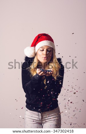 Beautiful teenage girl in casual clothes and Santa Claus hat holding and blowing confetti. Christmas themed portrait, studio shot, vertical, medium retouch. - stock photo