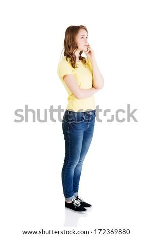 Beautiful teenage girl is thinking. Isolated on white background  - stock photo