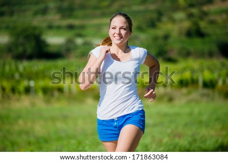 Beautiful teenage girl jogging in nature on sunny day