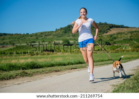 Beautiful teenage girl jogging with his pet (beagle dog) in nature - stock photo