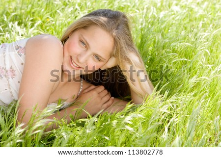 Beautiful teenage girl laying down on a long green grass garden, smiling at camera. - stock photo