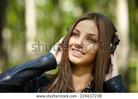 Beautiful teenage girl listening to music on her headphones outdoor - stock photo