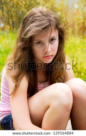 beautiful teenage girl looks serious outside in golden sunlight - stock photo
