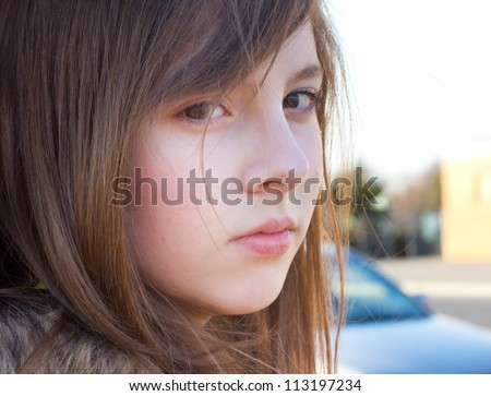 Beautiful teenage girl outside with a serious expression - stock photo