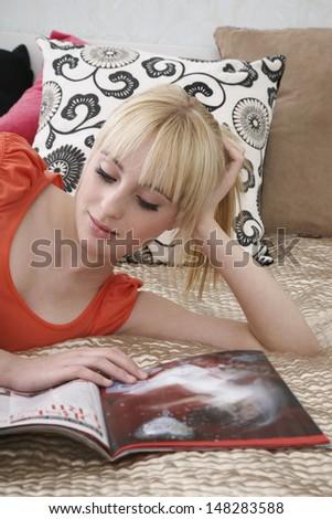 Beautiful teenage girl reading magazine while lying in bed - stock photo