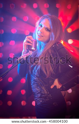 Beautiful teenage girl singer with a microphone, around smoke, color background, low key, no digital effect
