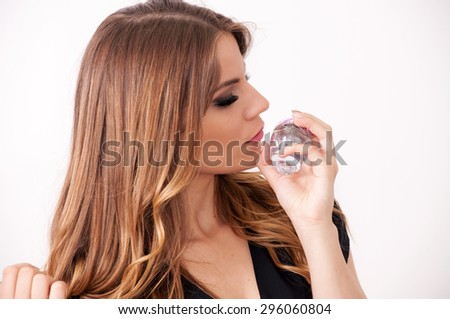 Beautiful teenage girl smelling perfume - stock photo