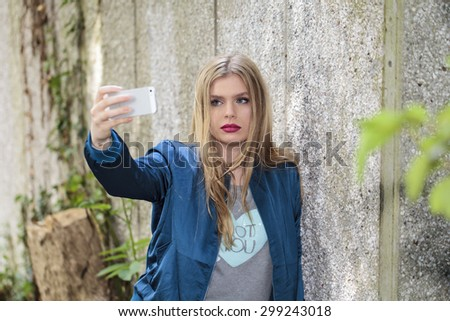Beautiful teenage girl taking photo with her phone - stock photo