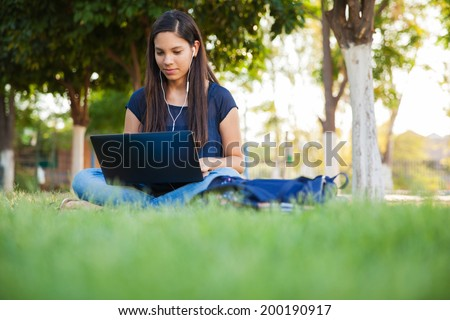Beautiful teenage girl using a laptop and earbuds outdoors