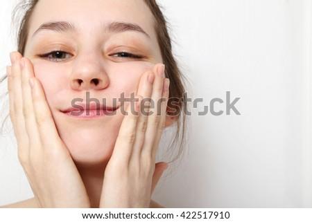 Beautiful  teenage girl washing her face   - stock photo