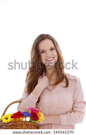 Beautiful teenage girl with fresh flowers in a wicker basket on her arm giving the camera a lovely friendly smile isolated on white