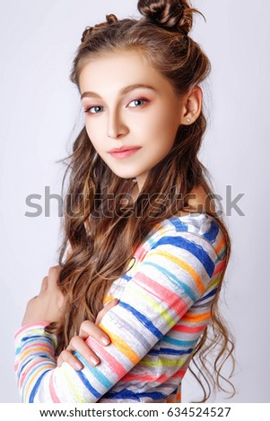 beautiful teenage girl with long curly hair on a white background. Studio  photo. Dressed