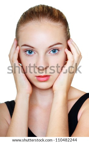 beautiful teenage girl with perfect skin touching her face by hands and looking into the camera. Isolated on white background