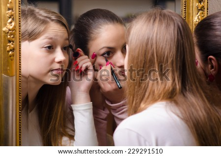 Beautiful teenage girlfriends having fun while putting make up in front of the old mirror. - stock photo