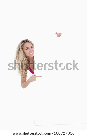 Beautiful teenage showing a great smile while pointing her finger at a blank poster