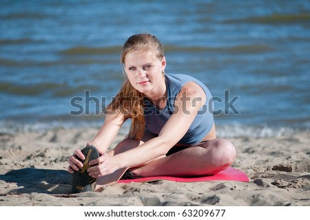 Beautiful teenage sport woman   doing stretching exercise on sand beach. Yoga - stock photo