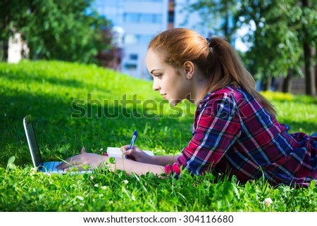 beautiful teenage student or school girl lying in park with laptop - stock photo