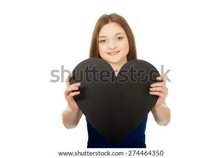 Beautiful teenage woman holding paper heart. - stock photo