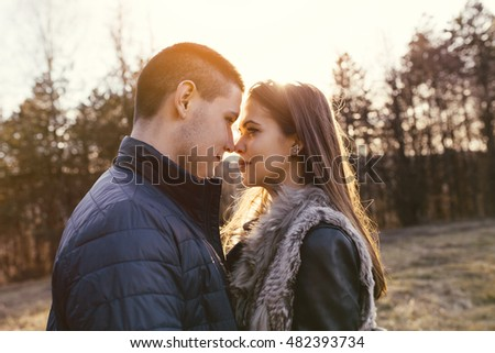 Beautiful teenager couple hugging and kissing. They enjoy autumn nature outdoors. Warm sunlight, flare and strong back light.