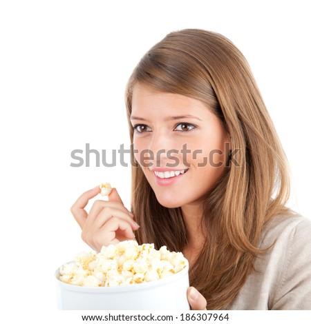 Beautiful teenager eating popcorn, studio shot - stock photo