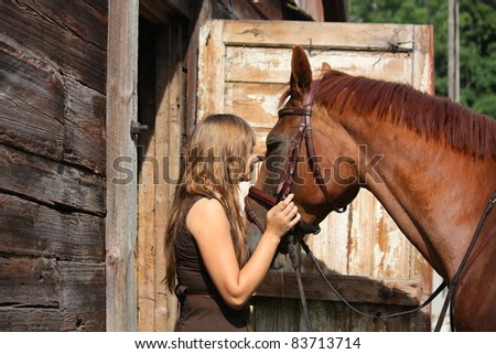 Beautiful teenager girl in brown dress and brown horse standing near the door of wooden house - stock photo
