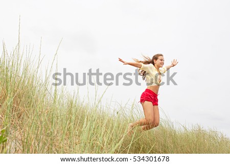 Beautiful teenager girl jumping up high against the sky on a coastal destination beach holiday, active in sand dunes with long grass, space outdoors. Fun energetic youthful lifestyle, nature exterior.