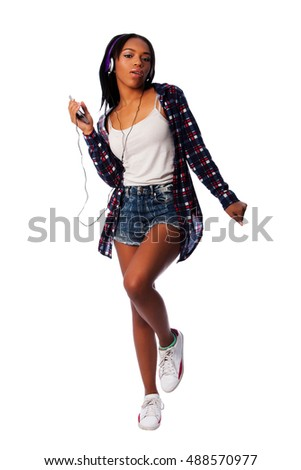Beautiful teenager girl listening, dancing and jamming to music on mobile phone wearing purple headphones, on white.
