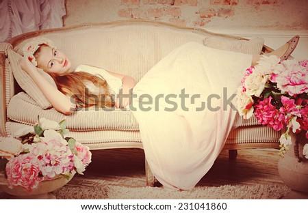 Beautiful teenager girl lying on sofa near flowers  - stock photo