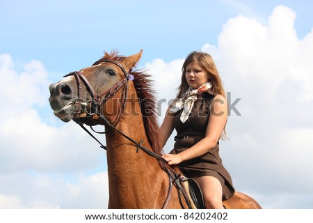 Beautiful teenager girl riding chestnut horse on sky background