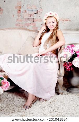 Beautiful teenager girl sitting on sofa and looking at camera - stock photo