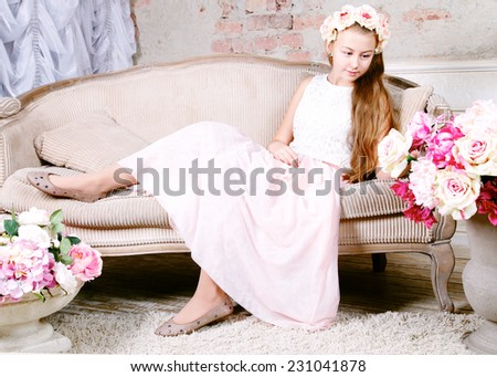 Beautiful teenager girl sitting on sofa and looking at flowers  - stock photo