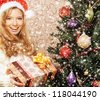 Beautiful teenager girl with the present near the Christmas tree - stock photo