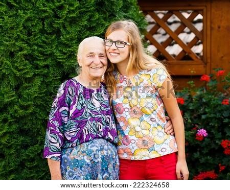 Beautiful teenager granddaughter visiting kind grandmother at the nursing home. - stock photo