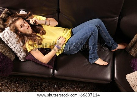 Beautiful teenager laying in a sofa and talking phone with friends
